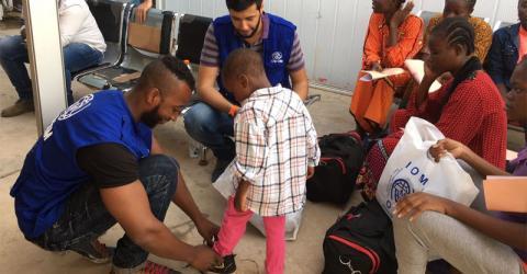 Niños nigerianos migrantes obtienen ropa nueva y zapatos antes de regresar a su país desde Libia. Foto: OIM 2016