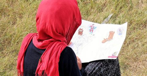 A woman at the Abu Salim detention centre passes the time drawing. Photo: IOM