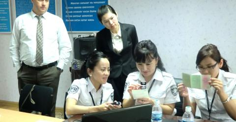 Mongolian immigration officers study fraudulent travel documents. © IOM 2015