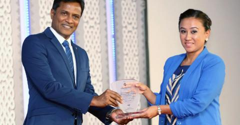 Maldives Minister of Home Affairs Hon. Umar Naseer (left) presents a service award to IOM Maldives project manager Shareen Tuladhar. Photo: Police.MV