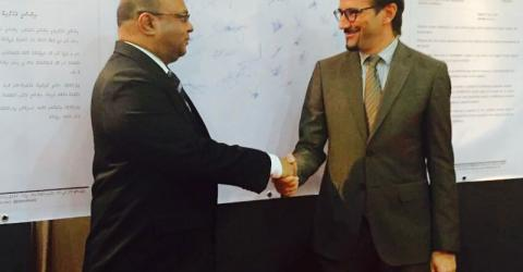 Chief Justice Abdullah Saeed (left) and IOM Chief of Mission Giuseppe Crocetti shake hands in front of the pledge to stop human trafficking in the Maldives. Photo: IOM 2016
