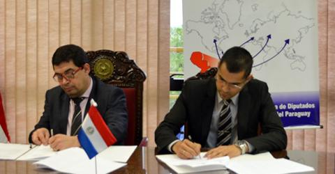 From left: The President of the Honorable Chamber of Deputies, Hugo Velázquez Moreno and IOM Head of Office in Paraguay, Richard Velázquez at the signing ceremony. © IOM 2015