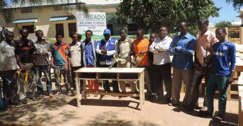 Twenty-five young people who are currently training as carpenters in a Baidoa town-based project funded by the Common Humanitarian Fund (CHF) and implemented by IOM and a local partner – Rural Education and Agriculture Organization (READO) – make desks and benches for Baidoa Primary and Secondary Schools. ©IOM/READO 2015