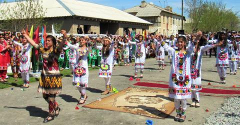 Jóvenes mujeres y muchachas de Tayikistán bailan en la inauguración del nuevo mercado ubicado en la frontera entre su país y Afganistán. Foto: OIM.