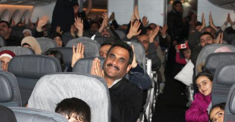 Syrian refugees resettled from Turkey cheer as their plane lands in Canada. Photo: IOM