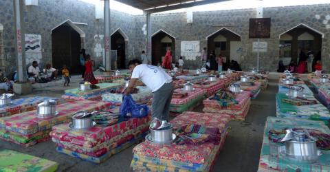 La photo montre une équipe de l'OIM distribuant des kits d'aide non alimentaire dans une école.
