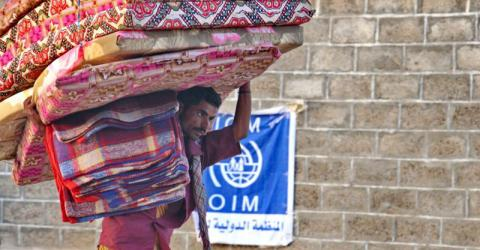 A displaced man carries bedding for his family following an IOM distribution at a local school. Photo: IOM