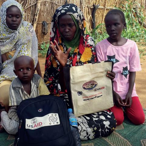 Meriam sits with three of her children while telling her story to NADA staff after receiving their dignity kits.