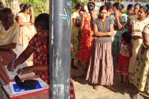 Affected families in the village of Pandariyaveli line-up and register to receive non-food items from IOM. © IOM 2012