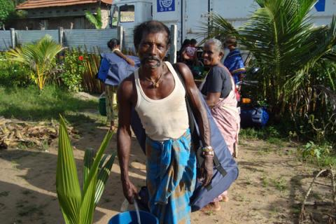 Families in the village of Pandariyaveli receive emergency relief kits from IOM. © IOM 2012