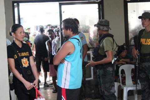 Habitants de Tanuan faisant la queue devant le bureau du maire pour obtenir une aide alimentaire et médicale