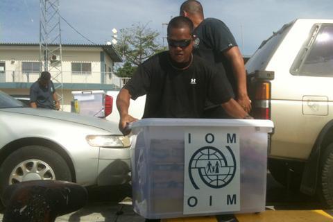 Des membres du personnel de l'OIM Micronésie préparent des provisions qui seront livrées à bord d'un pétrolier échoué sur un récif près de Pohnpei. © OIM 2014