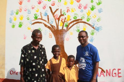 "The ""Tree of Life"" mural that IOM staff painted together with the children and other volunteers on a main wall in the village. © Nicola Simmonds/IOM 2013"