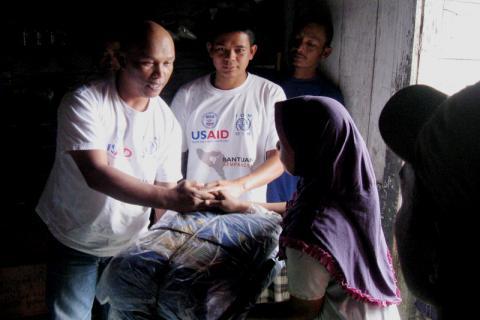 Personnel d'intervention d'urgence de l'OIM et volontaires distribuant des kits d'abris à Bener Meriah, dans la province d'Aceh, en Indonésie. © OIM 2013