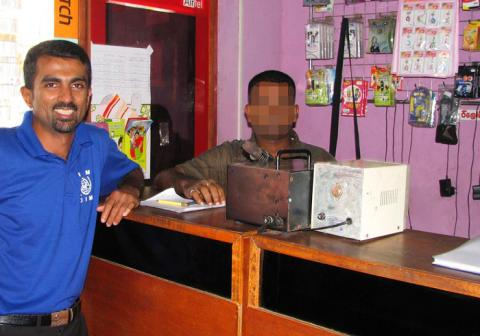 IOM project coordinator Subodha M. Malawara Arachchi and the beneficiary at the telecommunications shop. © IOM 2012