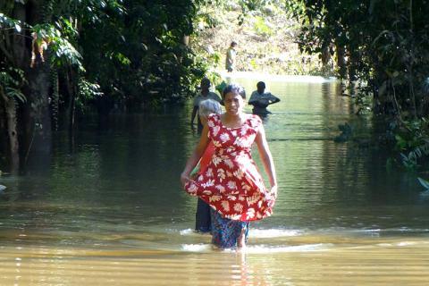 Aarachchika Nilankani Pushpakumari progresse péniblement sur une route inondée pour atteindre un point de distribution de l'OIM, au sud de Colombo, ce week-end. © OIM 2014