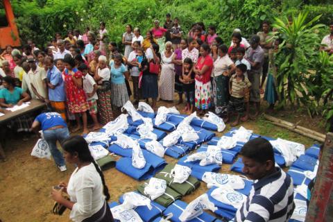 Le personnel de l'OIM et des autorités locales préparent des trousses de secours en cas d'inondation destinées à être distribuées. © OIM 2014
