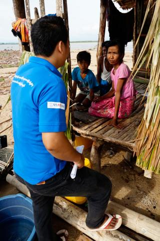 An IOM staff speaks with a migrant family in Ye township, southern Mon State in Myanmar. Significant numbers of households devastated by Cyclone Nargis in 2008 have migrated for work to southern Myanmar, where they face renewed risk of natural disaster. © IOM 2013