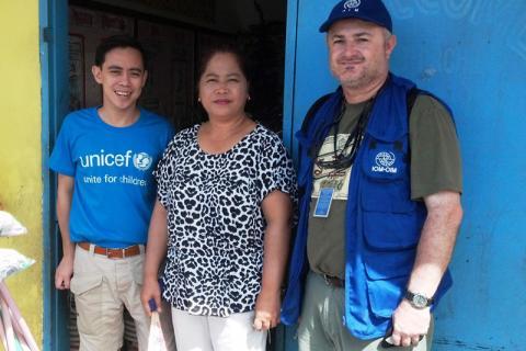 De gauche à droite : Raoul Bermejo, de l'UNICEF, Edna Azcarraga, la directrice de l'école, et Grant Robertshaw, de l'OIM, à l'école primaire Doña Victoria Cortes Memorial, dans la province de Capiz, aux Philippines. © OIM 2013