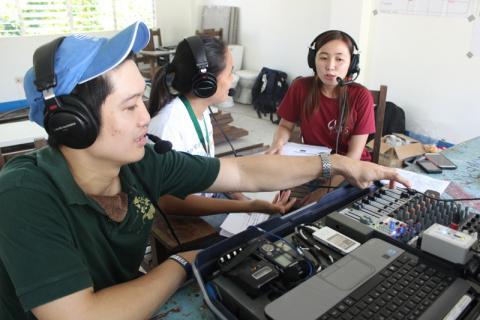 Los participantes en las prácticas en vivo y en directo de First Response Radio entrevistan a la representante de una ONG en el estudio improvisado (© OIM 2014/ Fotografía de Naomi Mihara)