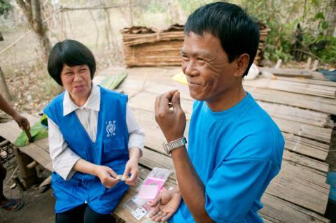 Dr Upin Katikut watches Tzing (47) take his daily TB medication in Pang Mu village, Northern Thailand.  © Mikel Flamm 2013