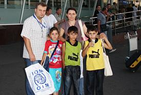 Natalia, her daughter Lina and sons Andrei and Mizger are met by IOM Ukraine staff on arrival in Kyiv. © IOM 2012 (Photo: Varvara Zhluktenko)