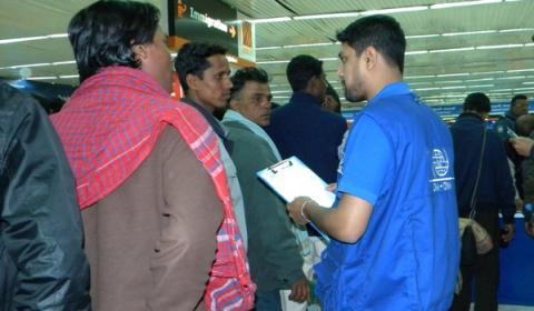 IOM staff assists Bangladeshi nationals who arrived home after fleeing the conflict in Libya. © IOM 2011