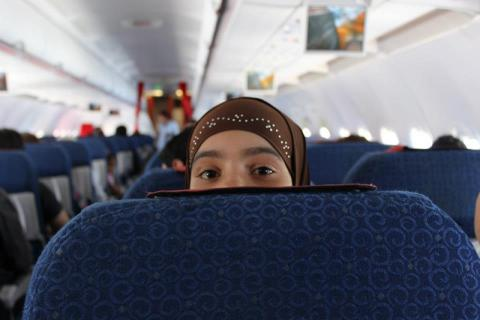During the cultural orientation sessions, staff encourage the refugees to keep their seatbelts fastened throughout the flight. This young boy kept telling his siblings to fasten their seatbelts and to remain seated. © IOM 2013 (Photo by Samantha Donkin)