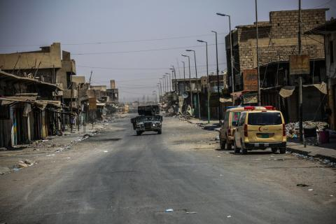 a military vehicle drives down an empty, damaged street in Western Mosul.