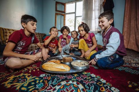A Syrian refugee family enjoys the meal they have received from one of the soup kitchens in Gaziantep that IOM supports. Photo: IOM / Muse Mohammed