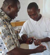 El Dr. Clement Jafani Nabare enseña al Dr. Afoko (médico residente) a utilizar un instrumento durante una clase para estudiantes de Medicina de Tamale especializados en urología mínimamente invasiva.