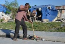 """Volunteers now clean many of Cite Soleil's garbage-strewn streets as this community in metropolitan Port-au-Prince rebrands itself and turns its back on an ill-deserved reputation as a """"no-go"""" area in Haiti. © IOM 2011"""