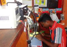 The beneficiary at work in his telecommunications shop. © IOM 2012