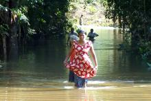 La Sra. Aarachchika Nilankani Pushpakumari trata de desplazarse en medio de las inundaciones para llegar al centro de distribución de la OIM localizado al sur de Colombo. © OIM 2014