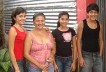 Griselda (second from left) and her three youngest children, Sara, (left); Suany (right of Griselda) and Josué, pose in front of the one room structure with dirt floors and sheet metal and cardboard walls she shares with her five unmarried children. © IOM 2011 (Photo: Renata Calderón)
