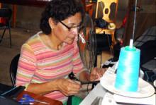 Socorro Morales, retornada nicaragüense de 54 años, trabajando en su máquina de coser, equipo que forma parte de la asistencia recibida por la OIM.  El programa de retorno voluntario asistido, financiado por Suiza, concede 3.000 francos suizos a cada retornado con los que pueden crear una empresa o volver a la escuela. © OIM 2012
