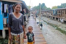 Itijah Subahan and her grandson at their new temporary home in Mampang, where they live with several hundred other Badjao families © IOM 2014 (Photo by Naomi Mihara)