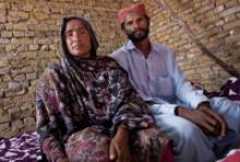 Premchand and his wife Sahiba in the new house they built through IOM's help. Aside from technical support, half of the bricks, the wooden door, window frames and materials for the roof were given by IOM. © IOM 2010 (Photo: Marco Bottelli)