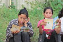 Mae Hong Son migrant workers reading IOM comic book with malaria and personal protection messages. © IOM 2014