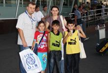 Natalia, sa fille Lina et ses fils Andrei et Mizger, sont accueillis par un employé de l'OIM Ukraine à leur arrivée à Kiev.