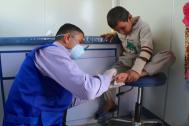 An IOM doctor treats a child in Hasan Sham camp, Iraq. Photo: IOM