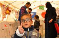 Un muchachito en Iraq usando los anteojos donados por Japón. Foto: OIM
