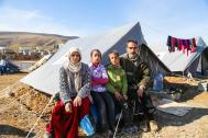 A Syrian family from Aleppo sit outside their tent donated by Japan in Basirma camp, Erbil, northern Iraq. (File photo.) IOM 2014.