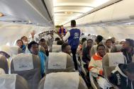 Migrants on board a plane taking them back to Guinea Conakry, from Libya. Photo: IOM