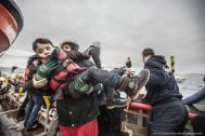 A young Syrian child is lifted to safety by responders from an overloaded boat carrying 55 migrants. File photo. Photo: MOAS/ Jason Florio 2016