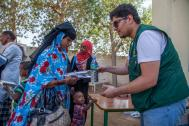 KSrelief support staffer gives refreshments to families who arrive in Berbera on the first KSrelief-funded evacuation boat from Yemen. Photo: IOM /  Mary-Sanyu Osire