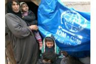 An internally displaced Syrian family driven from their home by the war shelters under IOM plastic sheeting. © IOM