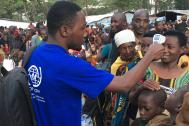 IOM staff takes the temperature of asylum seekers and refugees as part of a fit-to-travel medical exercise. Photo: IOM 2016