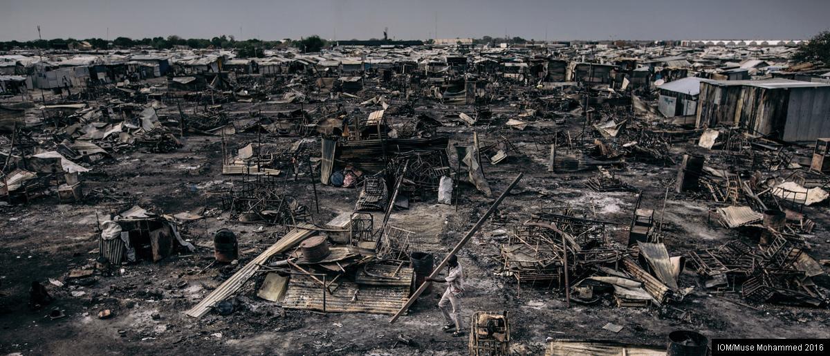 <br/>Site de protection des civils (PoC) de Malakal, Soudan du Sud. Un déplacé interne rassemble les restes de sa maison dans le Secteur 1 du Site de PoC de Malakal suite aux affrontements ethniques qui ont éclaté dans le camp après le décès de 18 personnes et de l'incendie qui a détruit des centaines d'habitations. Photo: OIM/Muse Mohammed