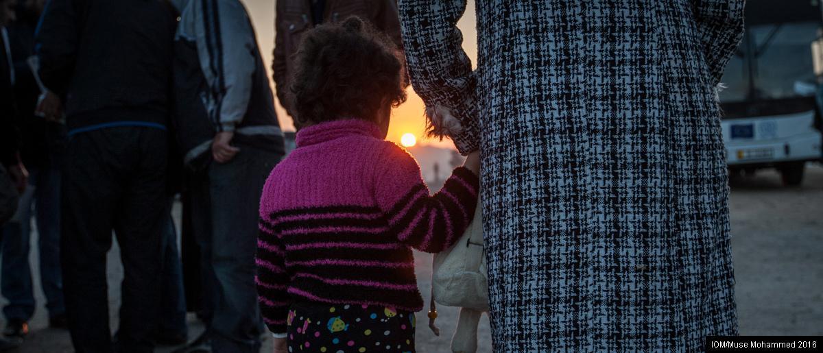 <br/>Amman, Jordanie: Une petite Syrienne enlace sa mère en attendant dans la file pour monter à bord d'un bus au point de rassemblement des réfugiés destinés à être réinstallés au Canada. Photo: OIM/Muse Mohammed